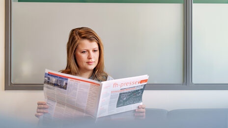 Foto einer Studentin, die in der FH-Presse liest.__A young woman reads the FH-Presse.